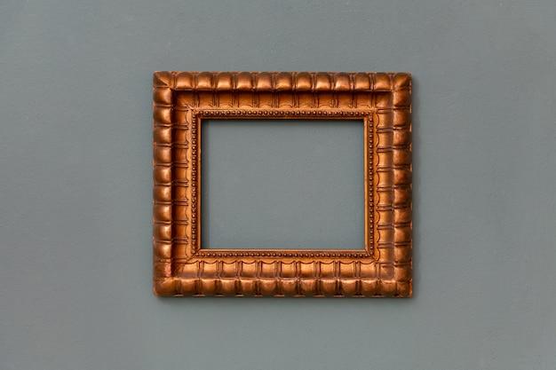 Verzierter goldener leerer rahmen, der zentriert an einer grünen wand mit copyspace für ein kunstwerk, ein bild oder ein gemälde hängt