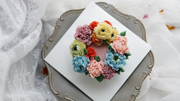 Verzierter kuchen mit blumen auf weißem hintergrund