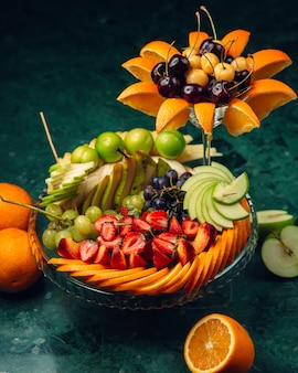 Verzierter obstteller mit geschnittenen früchten