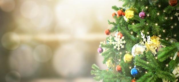 Verzierter weihnachtsbaum auf unscharfem hintergrund. tannenzapfen und schneeflocken
