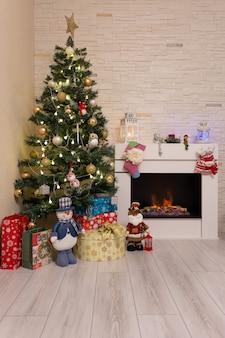Verzierter weihnachtsbaum, geschenke und weihnachtsdekorationen nahe brennendem kamin