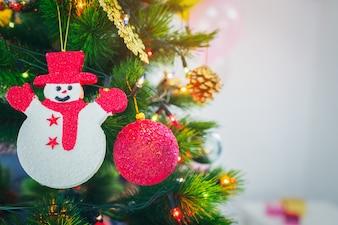 Verzierter Weihnachtsbaum mit dem Hängen des roten Balls, Schneepuppe
