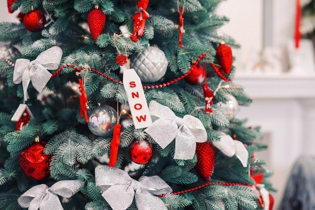 Verzierter weihnachtsbaum mit verschiedenen bunten spielzeugen darauf. schöne winterferien.