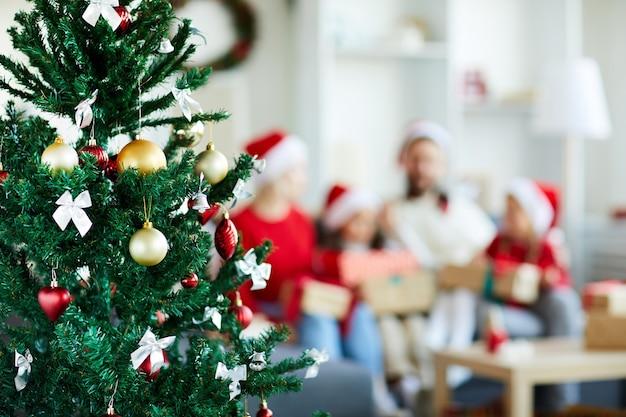 Verzierter weihnachtsbaum mit verschwommener familie