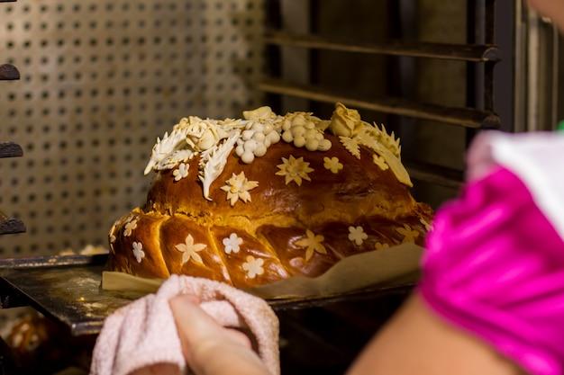 Verziertes brot auf ofenblech. gebackenes produkt von brauner farbe. hochzeitsbrot ist fertig. leckeres gericht für die zeremonie.