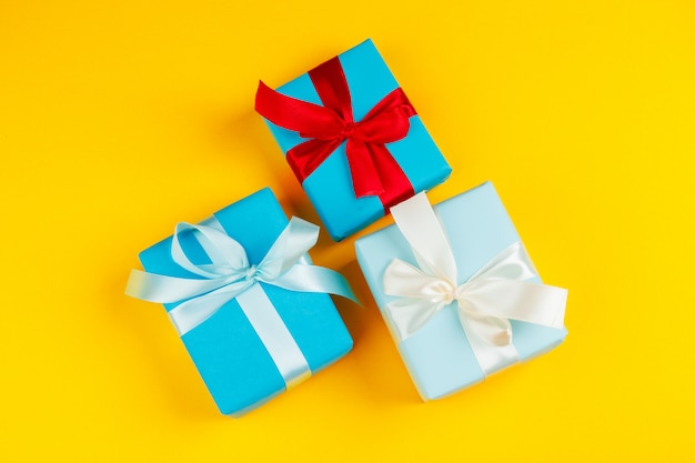 Verziertes farbiges geschenk auf gelbem flatlay