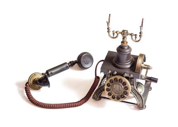 Verziertes retro-vintage-metalltelefon isoliert auf weißem hintergrund