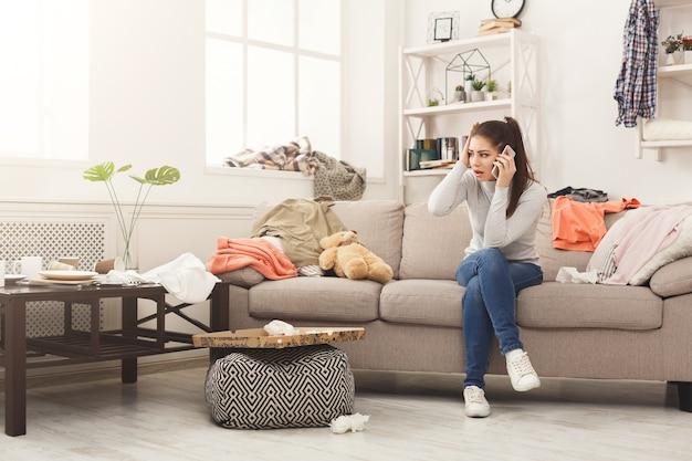 Verzweifelte frau sitzt auf dem sofa in einem unordentlichen zimmer sofa