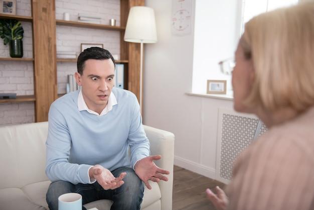 Verzweifelte lage. entsetzter attraktiver mann, der beim weinen mit dem leitenden psychologen kommuniziert