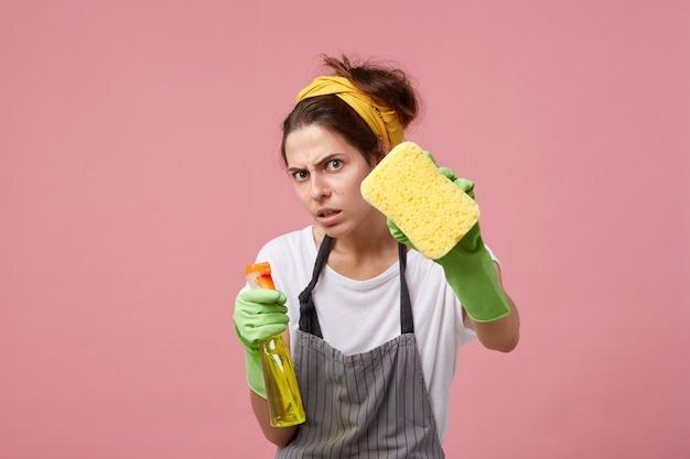Verzweifelte und peinlich saubere hausfrau, die fenster mit schwamm und reinigungsspray wäscht, während sie im haus putzt. junge europäische frau, die grüne gummihandschuhe trägt, die am wochenende aufräumen