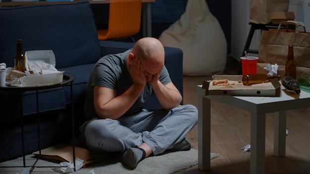 Verzweifelter hoffnungsloser mann, der allein auf dem boden sitzt und sich schwankt und selbstmordgedanken hat