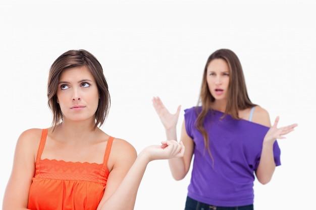 Verzweifelter jugendlicher, der aufrecht steht, während ihr freund sie anbrüllt