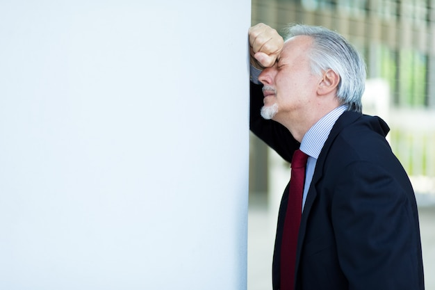 Verzweifelter manager, der gegen eine wand liegt