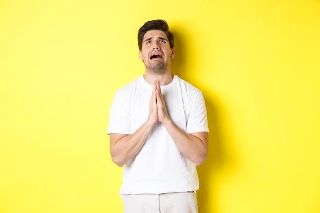 Verzweifelter mann, der gott bittet, händchen hält und betrübt aufschaut, über gelbem hintergrund stehend. platz kopieren