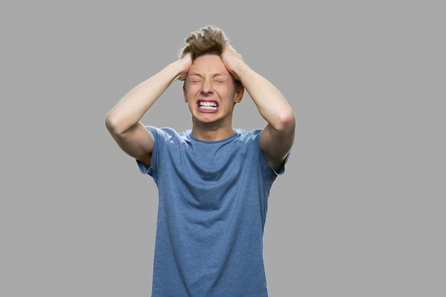 Verzweifelter teenager auf grauem hintergrund. gestresster wütender jugendlich junge, der schreit und seine haare zieht. konzept des nervenzusammenbruchs. menschliche negative ausdrücke.