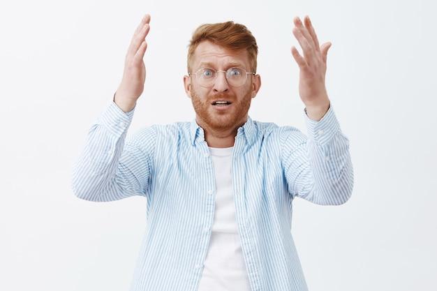 Verzweifelter verärgerter kerl, der seinen lieblingsspieler ansieht, der einen großen fehler macht, sich enttäuscht und schockiert fühlt und besorgt über die graue wand mit erhobenen händen und nervösem ausdruck in brille und hemd steht