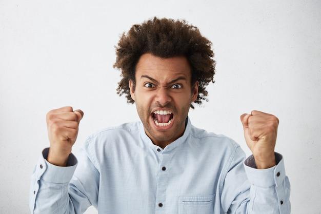Verzweifelter wütender wütender mann im weißen hemd, der seine fäuste ballte und laut schrie