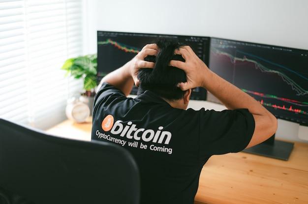 Verzweiflungsmann auf unten bitcoin-diagramm-markthintergrund auf lager
