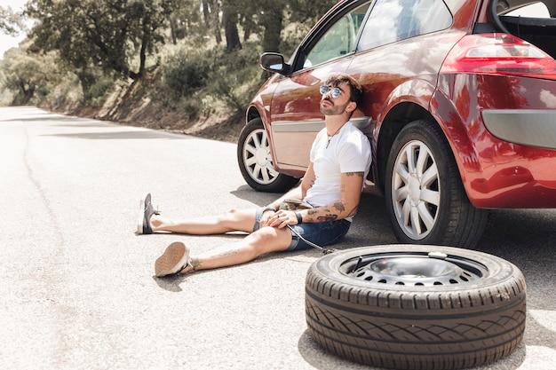 Verzweiflungsmann, der nahe dem aufgegliederten auto auf straße sitzt