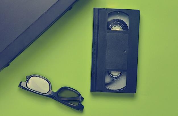 Vhs-player, videokassette, 3d-brille auf einer grünen oberfläche
