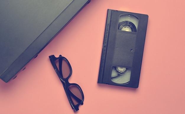 Vhs-player, videokassette, 3d-brille auf einer rosa oberfläche