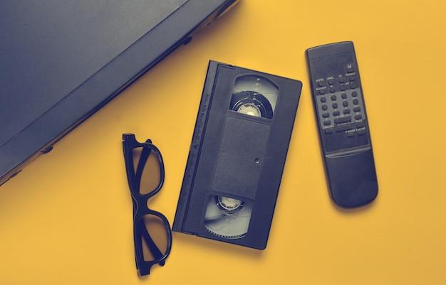 Vhs-player, videokassette, 3d-brille, tv-fernbedienung auf gelber oberfläche