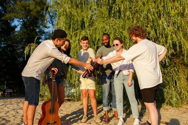 Vibes gruppe von freunden, die beim picknick am strand bei sonnenschein mit biergläsern anstoßen