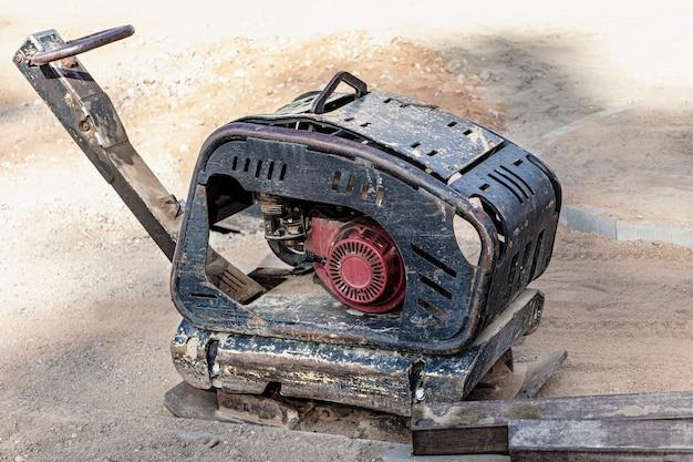 Vibrationsstampfer mit vibrationsplatte auf einer baustelle. verdichtung des bodens vor dem verlegen von pflastersteinen. nahaufnahme.