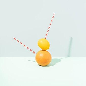 Vibrierende orange und gelbe zitrone auf weichem blauem pastellhintergrund. minimalistischer essensstil. Premium Fotos