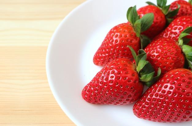 Vibrierende rote frische reife erdbeeren ausgerichtet auf einer weißen platte auf holztisch