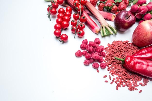 Vibrierender luftschuß des roten obst und gemüse auf einem weißen hintergrund