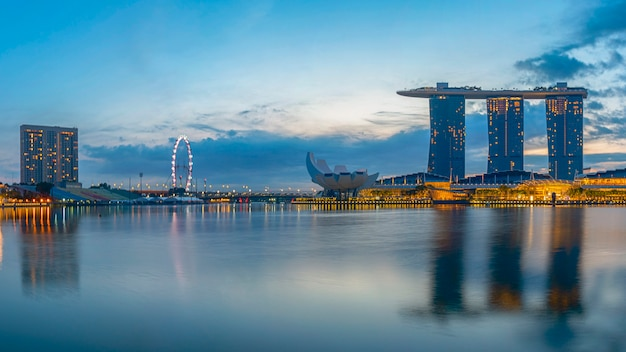 Vibrierender panoramahintergrund von singapur-stadtskylinen am modernen im stadtzentrum gelegenen gebäudebereich des geschäfts im sonnenaufgang