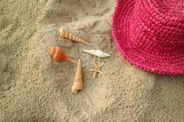 Vibrierendes rosa färbte strohhut auf dem sandigen strand mit vielen arten von kleinen muscheln, thailand