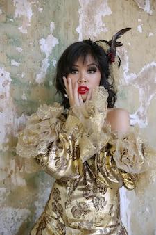 Victorian-kostümtrieb der chinesin tragender am schmutzgebäude