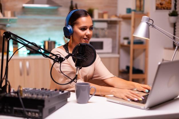 Video-blogger tippt auf laptop und nimmt stimme für podcast mit professionellem mikrofon auf