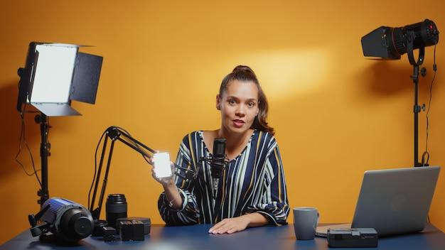 Video-bloggerin, die in ihrem professionellen studio-set einen mini-led-lichttest macht.