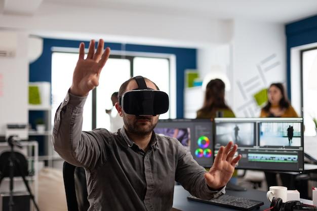Video-editor, der ein virtual-reality-headset erlebt, das bei der bearbeitung von filmmontagen gestikuliert