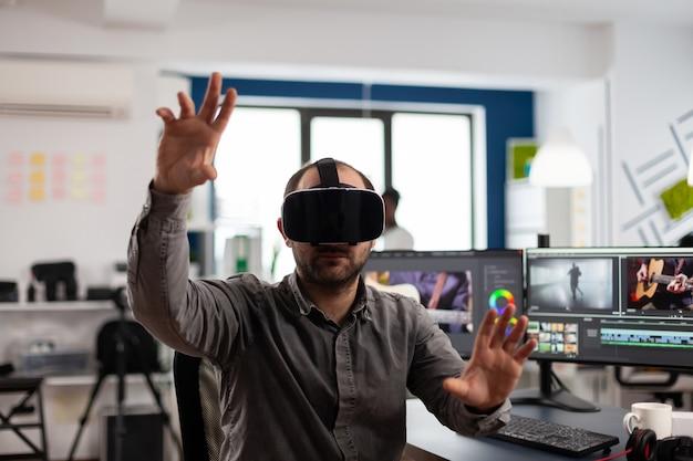 Video-editor, der ein virtual-reality-headset erlebt, gestikuliert, filmmontagen mit postproduktionssoftware bearbeitet, die im büro der kreativagentur arbeitet