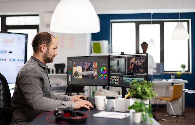 Video-editor, der filmmontage-schnittmaterial und ton mit postproduktionssoftware und zwei monitoren bearbeitet