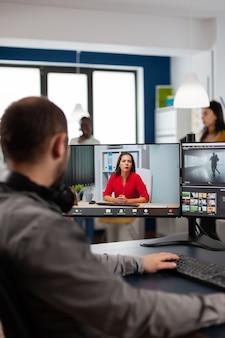 Video-editor, der mit remote-kunden in web-online-meeting über videoanruf-bearbeitungsprojekt spricht, feedback zu kommerziellen filmen mit postproduktionsprogramm auf zwei displays in der kreativagentur einholt