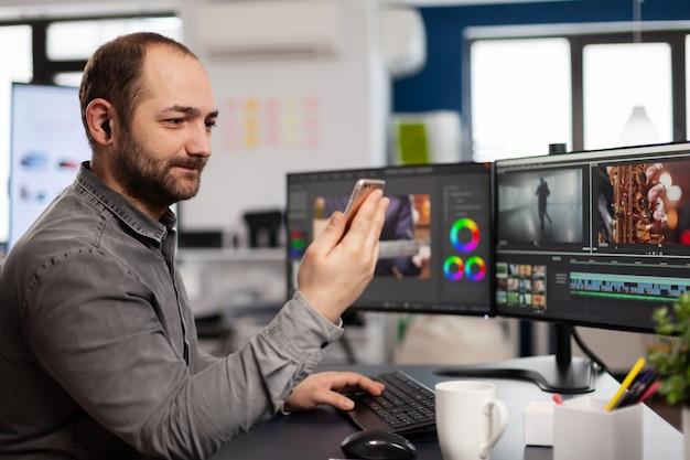 Video-editor, der über videoanruf mit dem kunden spricht, der smartphone-bearbeitungsfilm in der kreativagentur hält
