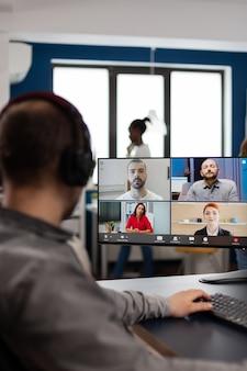 Video-editor-direktor, der mit dem kreativteam in einem web-online-meeting über die arbeit von videoanrufen spricht und feedback zu kommerziellen filmen mithilfe von postproduktionssoftware auf dem pc im kreativbüro erhält