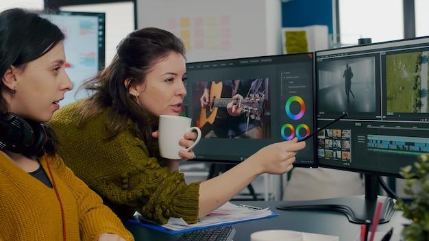 Video-editoren von kollegen diskutieren vor dem pc und arbeiten für kundenmaterial mit postproduktionssoftware und zwei monitoren