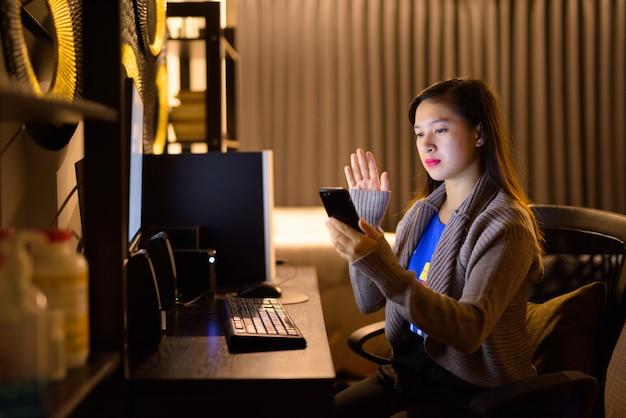 Videoanruf der jungen asiatischen frau mit telefon während der arbeit von zu hause
