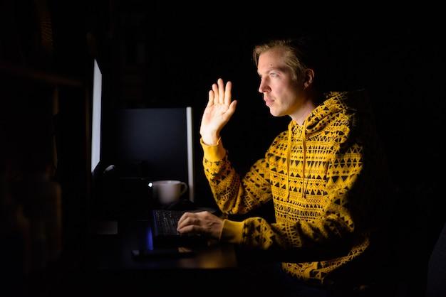 Videoanruf des jungen gutaussehenden mannes während der überstunden zu hause im dunkeln