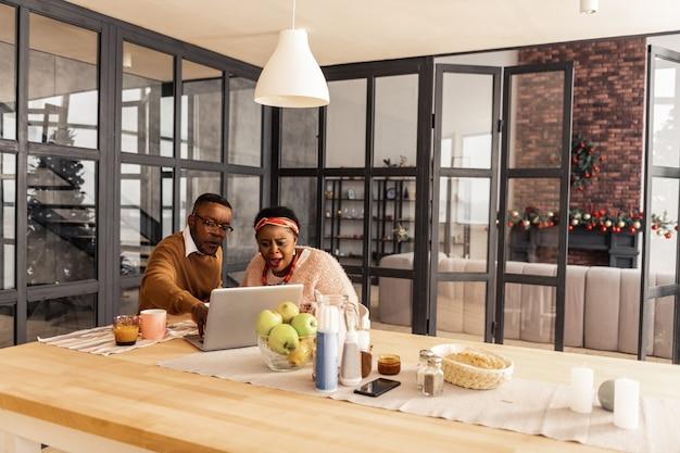Videoanruf. nettes angenehmes paar, das vor dem laptop sitzt und zu ihren verwandten ruft