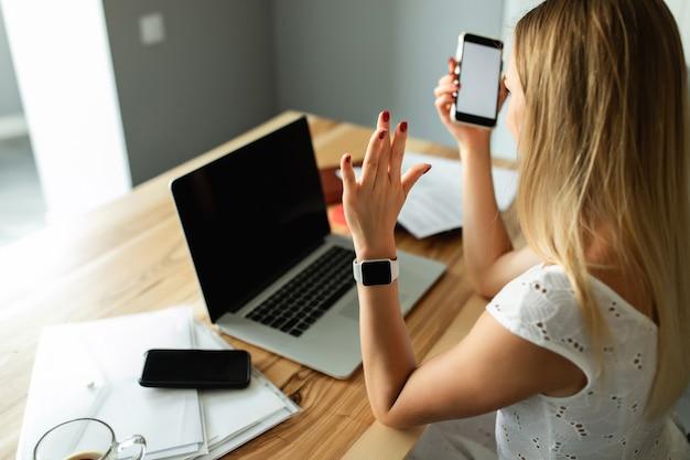 Videoanruf, videokonferenz mit anderen personen auf einem laptop in innenräumen. online lernen und arbeiten. frau mit laptop-computer, der zu hause büro arbeitet