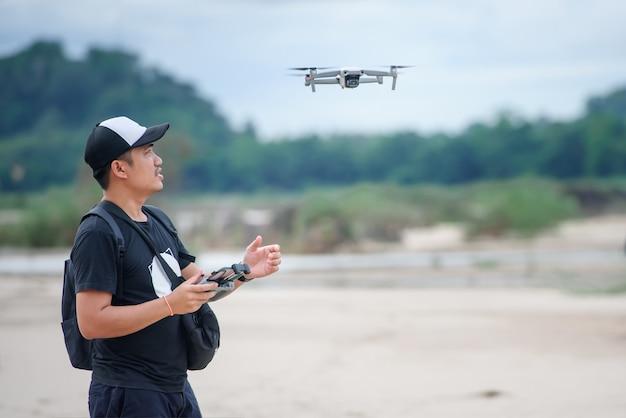 Videoaufzeichnung mit einem drohnenflugzeug asiatische männer verwenden videodrohnen, um musikvideos zu erstellen