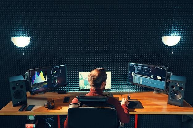 Videobearbeitung. professioneller editor mit speziellen soundeffekten. rückansicht des jungen mannes, der diagramme auf monitoren beobachtet. kopieren sie platz auf grauer wand