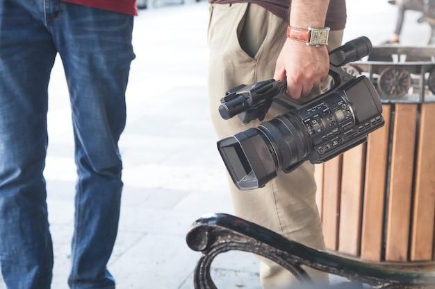 Videobetreiber, der professionelle videokamera in einer stadt hält.